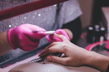 Una profesional haciendo la manicura a una mujer, en representación de maletín manicura
